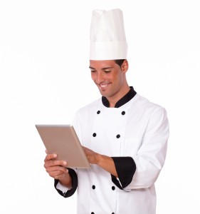 Handsome chef guy using his tablet pc